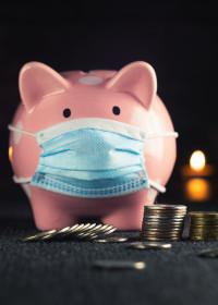 Pink piggy bank wearing a medical mask