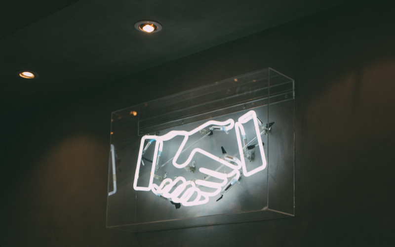 neon sign of two hands shaking