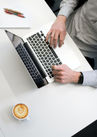 Man typing on computer next to coffee